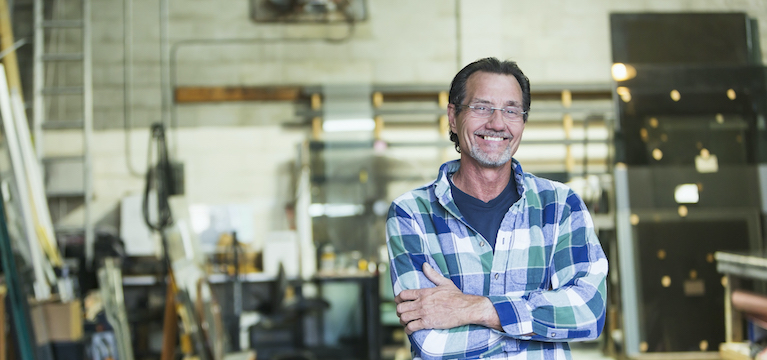 man in warehouse smiling at camera