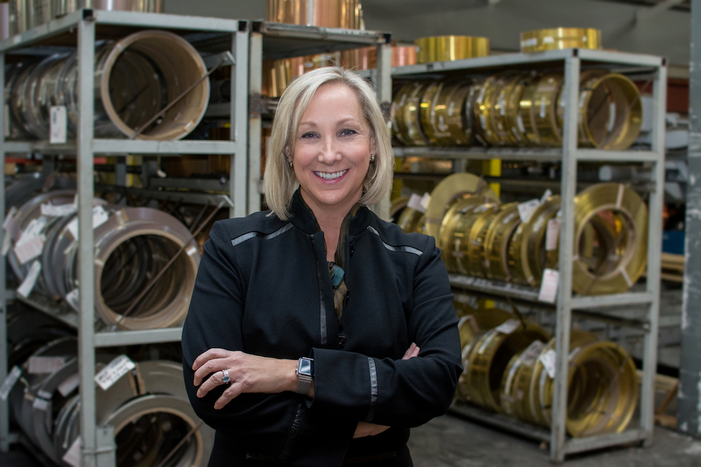 Sandy Crawford, President of Mead Metals with metal coils in the background.