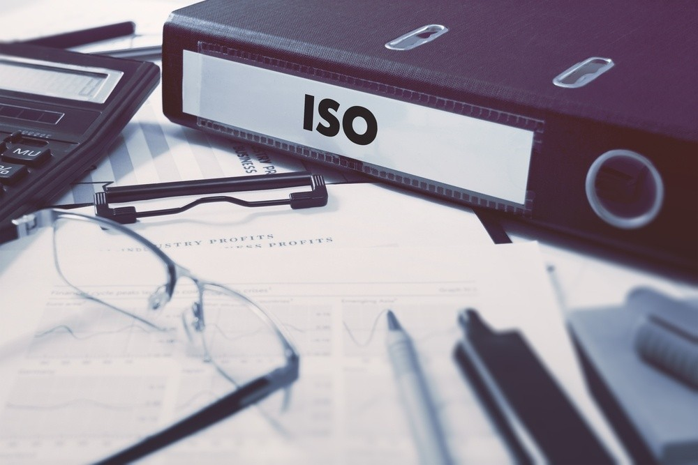Office folder with inscription ISO - International Organization for Standardization - on Office Desktop with Office Supplies. Business Concept on Blurred Background. Toned Image..jpeg