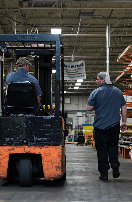 Two warehouse employees - one on fork lift and another walking alongside talking